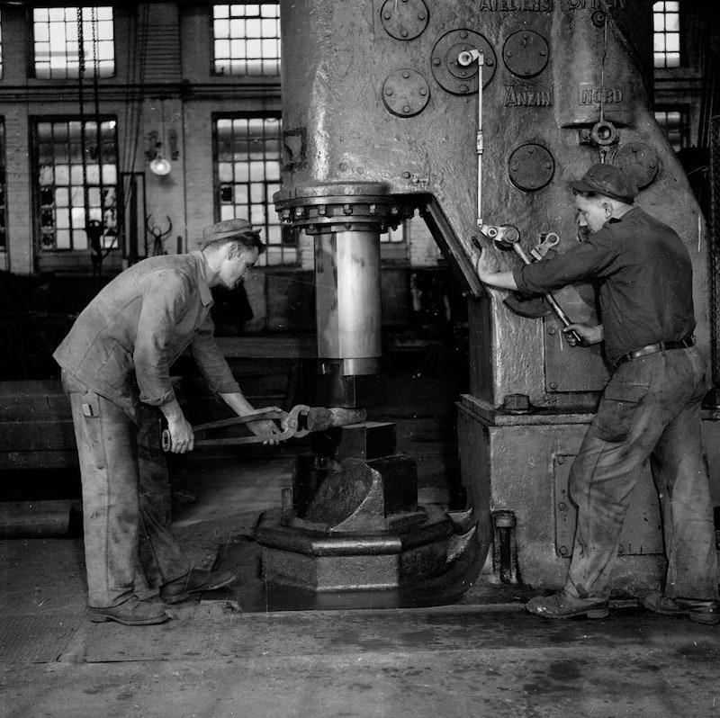 A l'atelier, deux ouvriers utilisant un marteau pilon © Son et Lumière