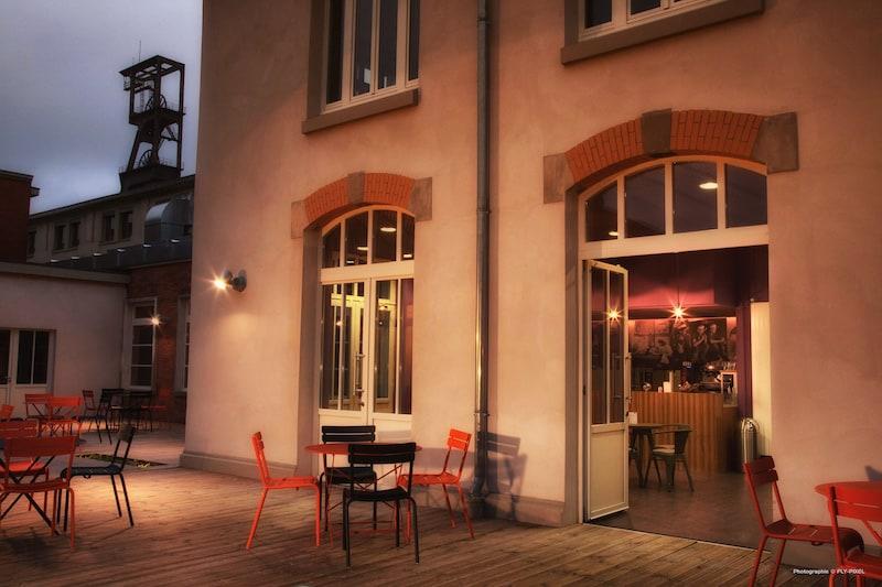 """terrasse extérieure de nuit de la cafétéria """"Le refuge des mineurs"""" équipée d'un mobilier orange et noir"""